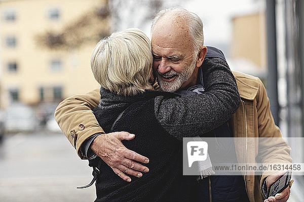 Lächelnder älterer Mann umarmt Partner während des Winters in der Stadt