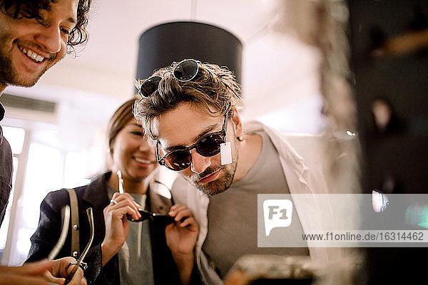 Lächelnder Mann probiert mit Freunden im Geschäft eine modische Brille aus