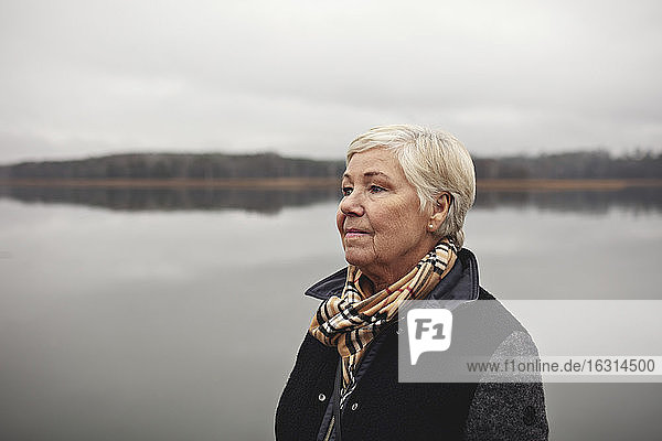Smiling wrinkled woman looking away by lake against clear sky