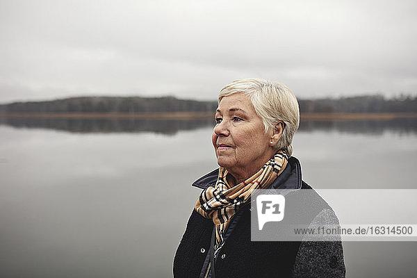 Lächelnde  runzlige Frau schaut am See gegen den klaren Himmel weg