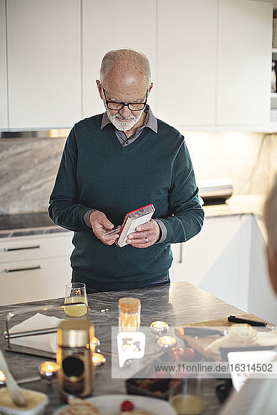 Senior man taking pills while standing by kitchen island at home