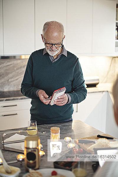 Älterer Mann nimmt Tabletten  während er zu Hause an der Kücheninsel steht