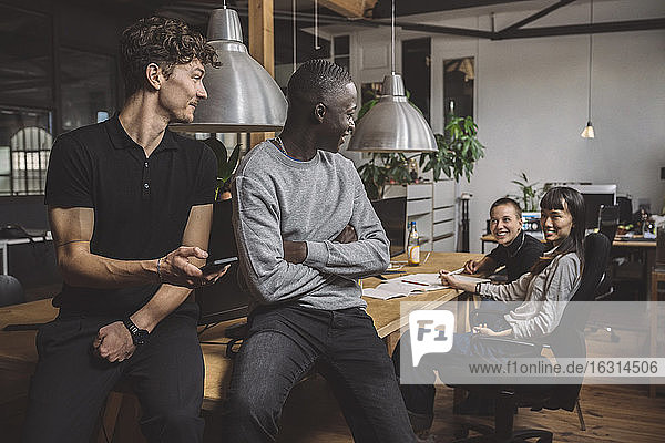 Lächelnde Geschäftsleute im Gespräch mit Kolleginnen am Arbeitsplatz