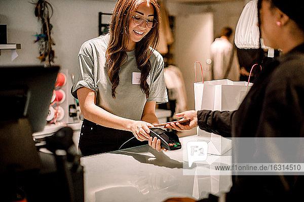 Weibliche Kundin bezahlt per Smartphone an lächelnde Verkäuferin im Geschäft