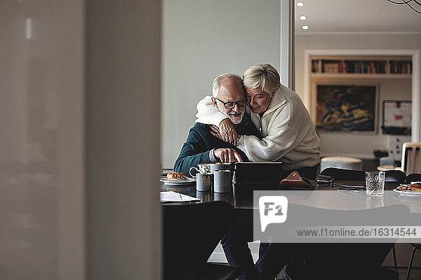 Lächelnde ältere Frau umarmt Partner am Esstisch im Wohnzimmer