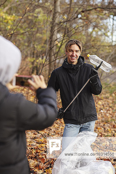 Teenager photographing friend with waste plastic bottle in park during autumn