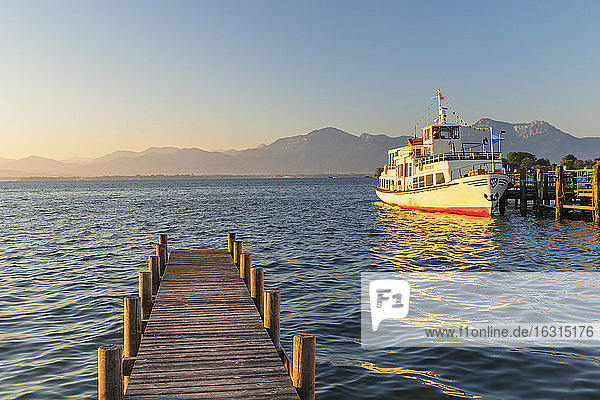 Excursion boat on a jetty at sunrise  Gstadt am Chiemsee  Lake Chiemsee  Upper Bavaria  Germany  Europe