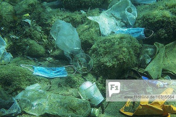 Auf dem Meeresboden liegt eine weggeworfene gebrauchte medizinische Gesichtsmaske zusammen mit anderen Plastikabfällen  Plastik- und andere Müllverschmutzungen in der Adria. Becici  Gemeinde Budva  Montenegro  Europa