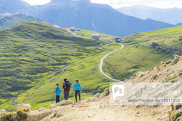 Mother with two little sons walking on path in green meadows towards Rifugio Sassopiatto  Dolomites  Trentino-Alto Adige  Italy  Europe