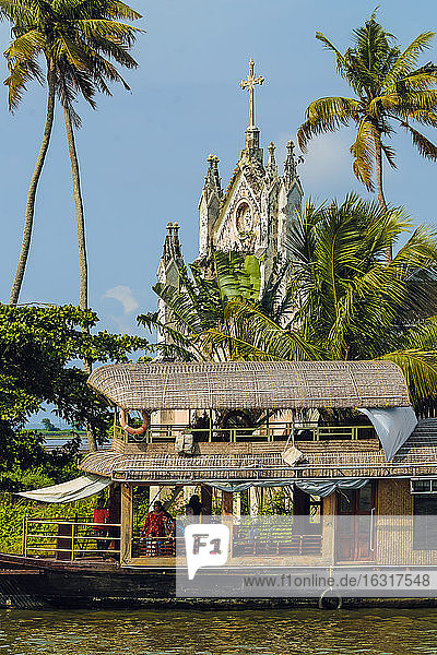 Old church with patinated facade and moored houseboat on a backwaters cruise visitor stop  Alappuzha (Alleppey)  Kerala  India  Asia