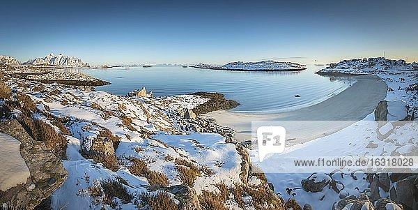 Verschneiter weißer Sandstrand in winterlicher Bucht  blaues Meer  hinten Lofotengipfel  Nordland  Lofoten  Norwegen  Europa