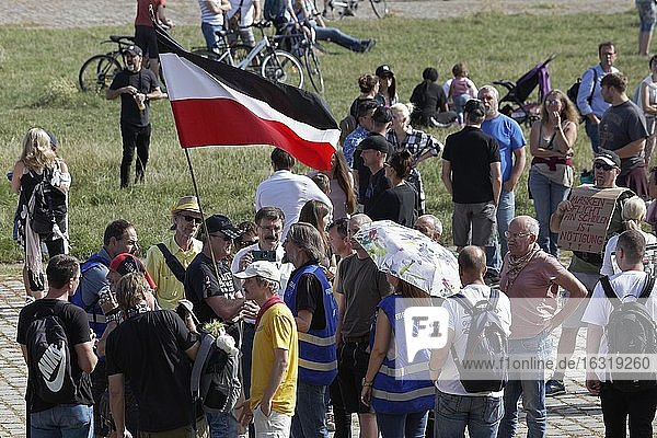 Demo against Corona rules on the Rhine meadows  man with forbidden Reich war flag  surrounded by people  Düsseldorf  North Rhine-Westphalia  Germany  Europe