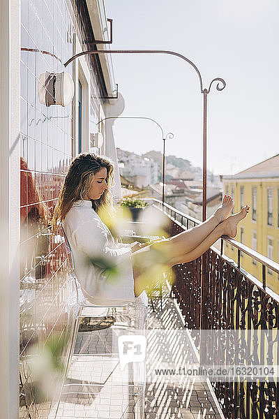 Young woman relaxing on sunny apartment balcony  Lisbon  Portugal