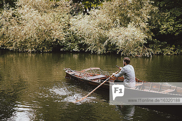 Man rowing canoe on tranquil River Avon  Bath  Somerset  UK