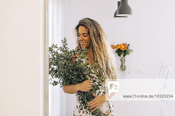 Smiling young woman holding bunch of fresh eucalyptus