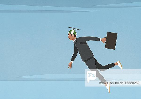 Businessman in propellor hat flying in sky