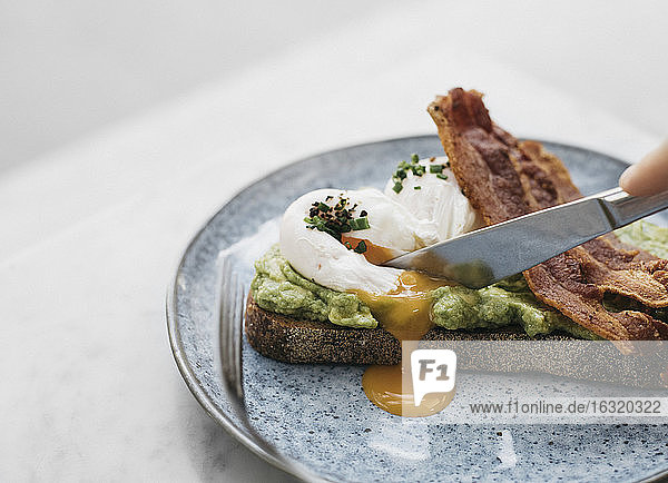 Knife cutting through avocado toast with egg and bacon