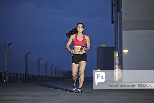 Young female Asian sportswoman jogging at twilight