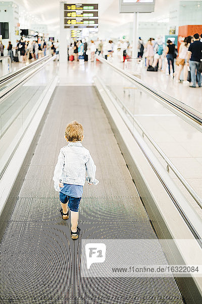 Spain  Barcelona  back view of little boy on moving walkway at the airport