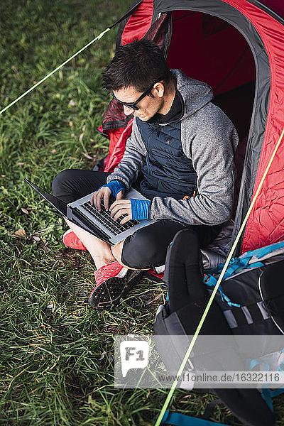 Man camping in Estonia  sitting in tent  using laptop