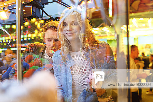 Young couple at fun fair looking at prizes in window
