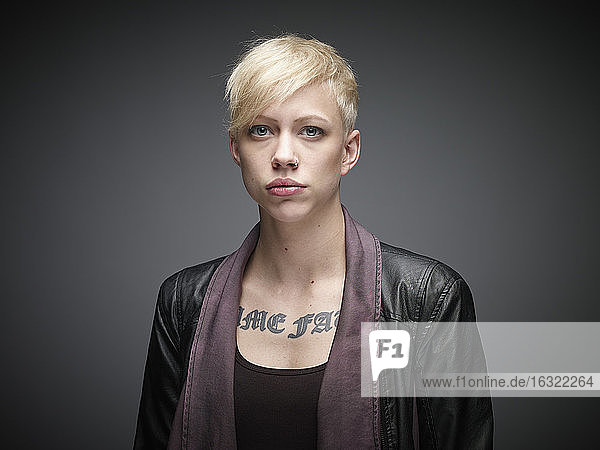 Portrait of blond young woman with tatoo in front of grey background