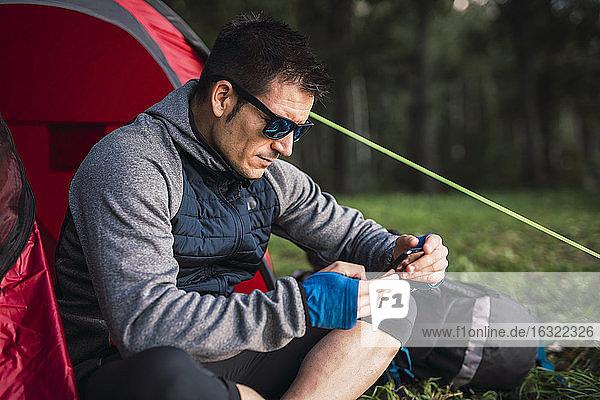 Man camping in Estonia  sitting in tent  using smartphone