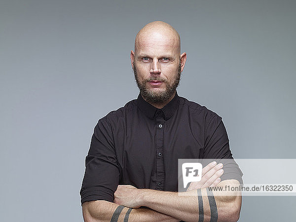 Portrait of man with bald and full beard in black in front of grey background