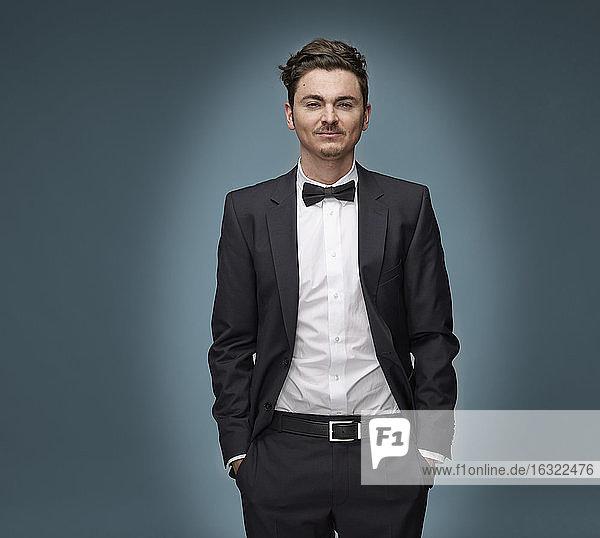 Portrait of arrogant looking man wearing suit and bow tie