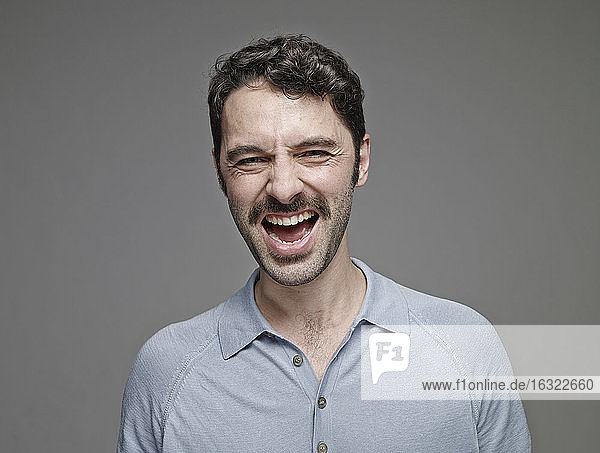 Portrait of screaming man in front of grey background