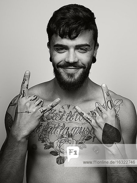 Portrait of grinning man with tatoo on his chest and hands