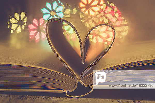 Heart shaped book pages in front of colourful lights