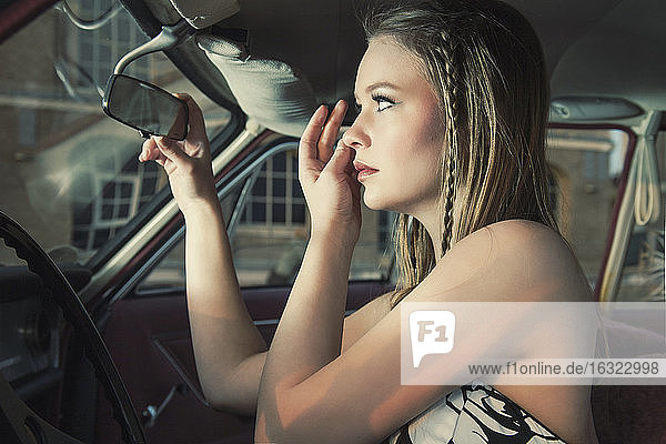 Young woman checking her make up in rear-view mirror of vintage car
