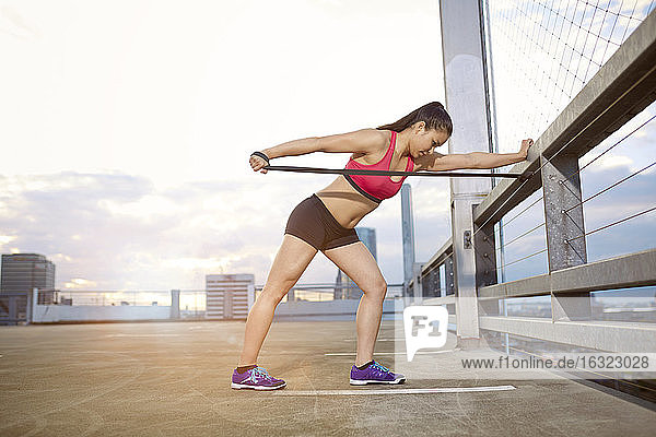 Young female Asian sportswoman doing stretching exercises with fitness band