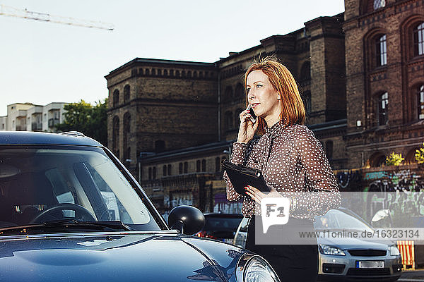 Portrait of businesswoman with file standing beside parked car telephoning