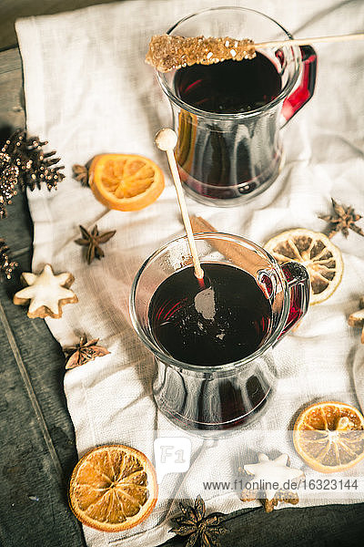 Glasses of mulled wine  orange slices and cinnamon stars on cloth and wooden tray