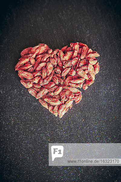 Wolfberries shaped like a heart on slate