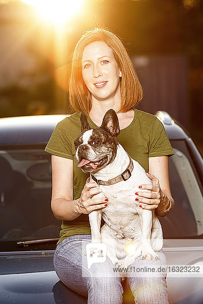 Portrait of redheaded woman sitting on car bonnet with her French bulldog