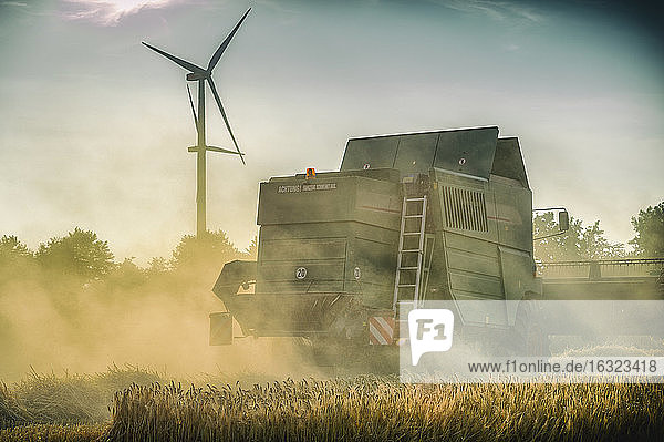 Germany  Grevenbroich  combine harvester on field and wind turbine