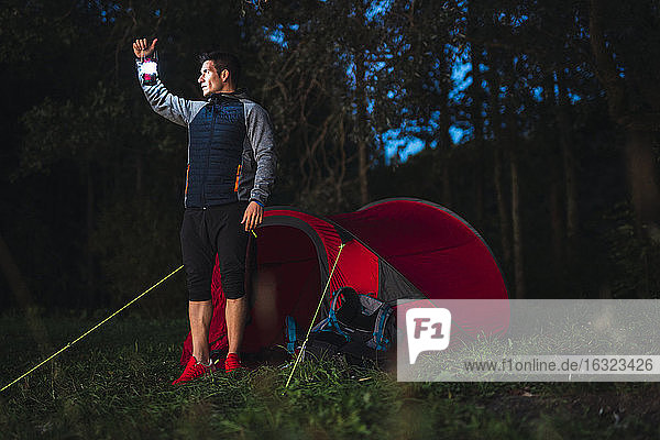 Man camping in Estonia  standiing in front of tent holding lantern