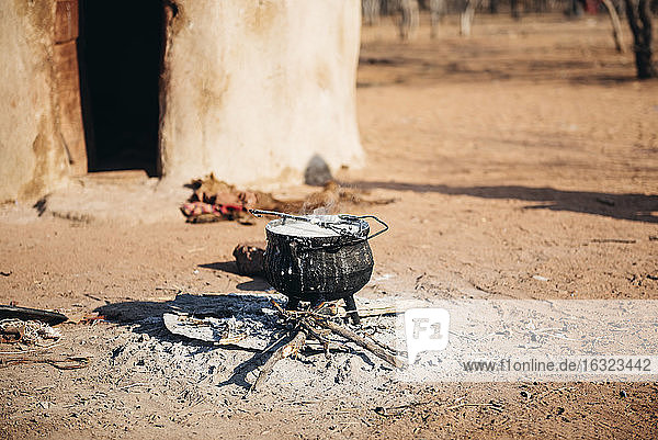 Namibia  Damaraland  iron pot boiling on a small fire in front a hut in a Himba village
