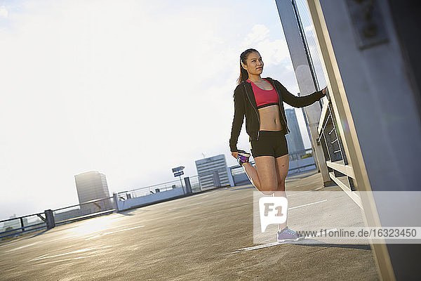Young female Asian sportswoman doing stretching exercises