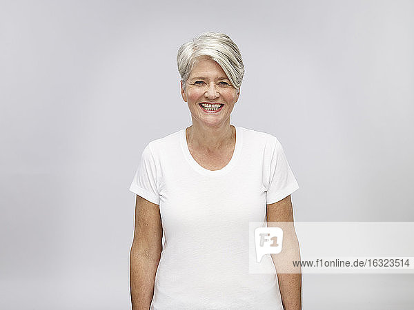 Portrait of mature woman with grey hair in front of light background