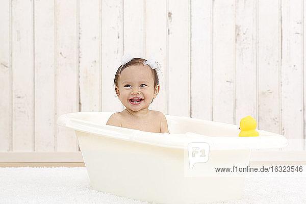 Porträt eines lachenden kleinen Mädchens beim Baden in einer Wanne