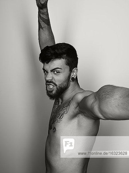 Portrait of angry shirtless man with outstretched arms
