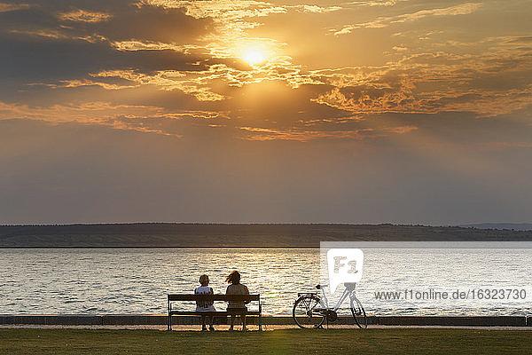 Austria  Burgenland  Illmitz  Lake Neusiedl  People sitting on bench at sunset