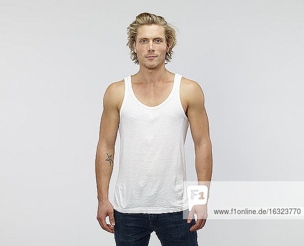 Portrait of young blond man wearing vest in front of white background