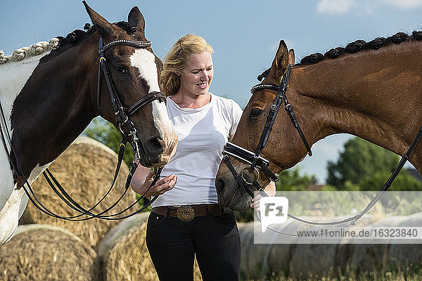 Germany  Wiesenau  blond woman with two horses