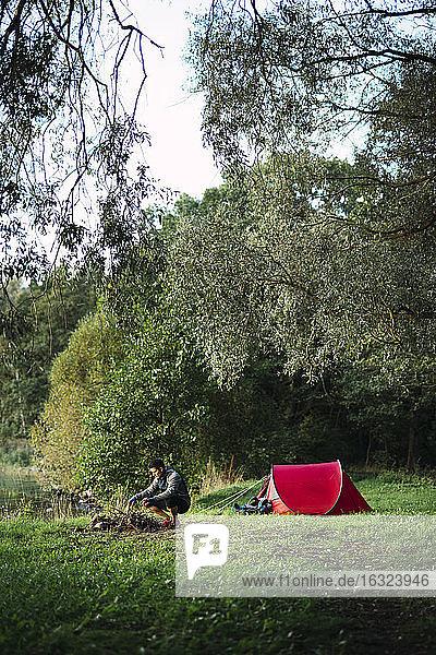 Man camping in Estonia  preparing campfire