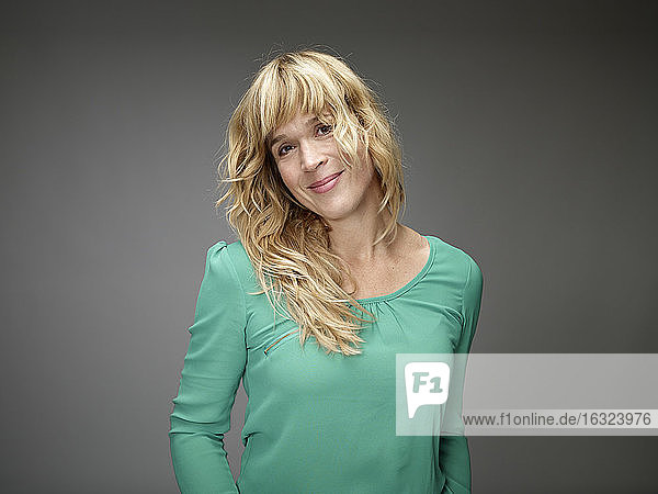 Portrait of smiling blond young woman in front of grey background